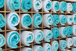 luxury and hygiene concept - close up of shelf with rolled bath towels at hotel spa